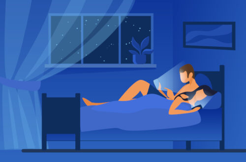 Couple lying in bed and using mobile phones